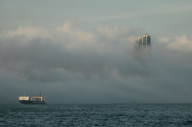 """The 67-storey-high """"The Masterpiece"""", one of Hong Kong's most luxurious high-rise residential buildings, is seen during foggy conditions under the influence of a warm maritime airstream at sunset in Hong Kong in this March 21, 2011 file photo. Hong Kong is expected to report trade data this week. (Photo by Tyrone Siu/Reuters)"""