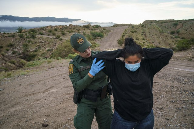 United States Border Patrol Agent Valeria Morales (L) searches an Ecuadorian woman who was caught trying to enter the United States undetected in Sunland Park, New Mexico on September 1, 2021. (Photo by Paul Ratje/AFP Photo)