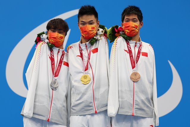 (L to R) China's silver medallist Weiyi Yuan, gold medallist Tao Zheng and bronze medallist Lichao Wang pose on the podium of the men's 50m freestyle S5 swimming competition during the Tokyo 2020 Paralympic Games at the Tokyo Aquatics Centre in Tokyo on September 1, 2021. (Photo by Marko Djurica/Reuters)