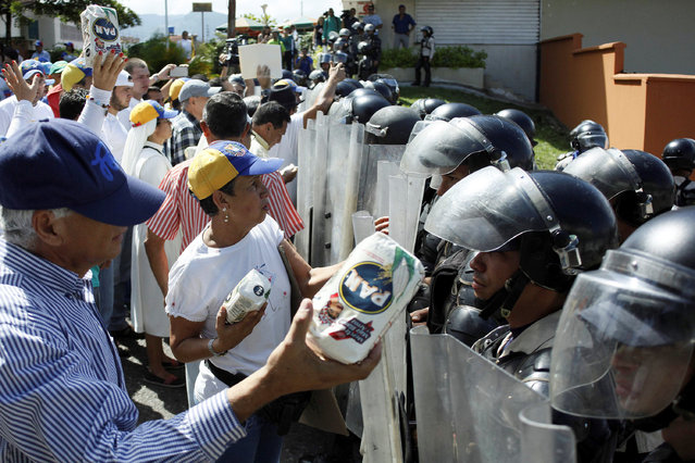 Opposition supporters hold packages of PAN corn flour in front of riot police during a rally against Venezuelan President Nicolas Maduro's government and to commemorate the 59th anniversary of the end of the dictatorship of Marcos Perez Jimenez in San Cristobal, Venezuela January 23, 2017. (Photo by Carlos Garcia Rawlins/Reuters)