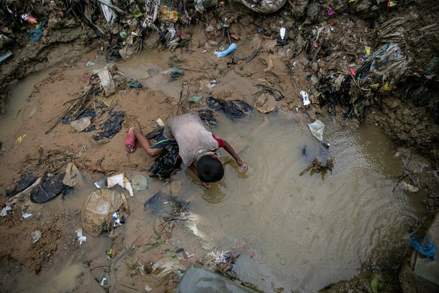 A child plays in a puddle during a rainstorm in a Rohingya refugee camp on August 11, 2021 in Cox's Bazar, Bangladesh. On Tuesday, Bangladesh started a COVID-19 vaccination drive for Rohingya refugees. Nearly 48,000 Rohingya refugees will be inoculated with the help of the UN agencies. (Photo by Allison Joyce/Getty Images)