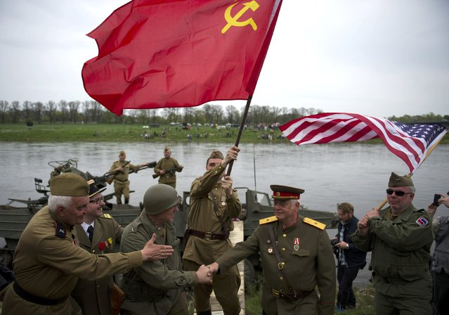 Members of a historical re-enactment group dressed as U.S. and Soviet Army soldiers take part in Elbe Day celebrations, in eastern German city of Torgau at the river Elbe, April 25, 2015. (Photo by Stefanie Loos/Reuters)