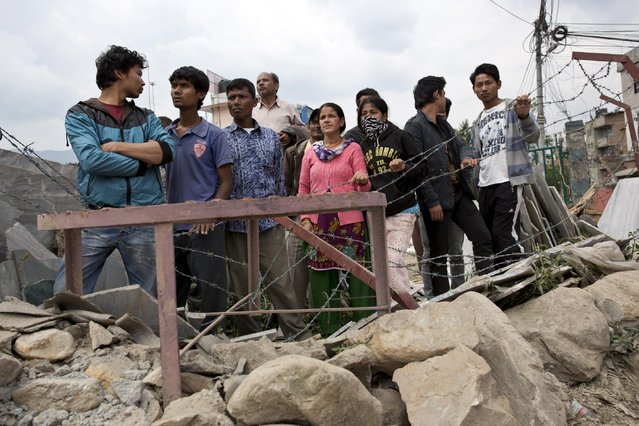 Locals gather to watch a rescue operation at the site of a budget hotel that collapsed in Saturday's earthquake, in Kalanki neighbourhood of Kathmandu, Nepal, Sunday, April 26, 2015. (Photo by Bernat Armangue/AP Photo)