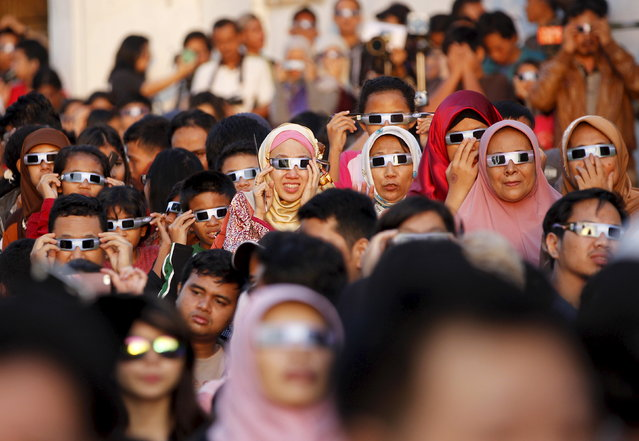 People watch a solar eclipse outside the planetarium in Jakarta, Indonesia March 9, 2016. (Photo by Garry Lotulung/Reuters)