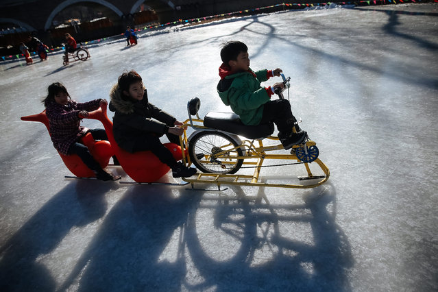 Chinese children ride sleds and an ice bicycle on the frozen surface at Longtan Park during the Spring Festival in Beijing, China, 30 January 2017. China continues to celebrate the annual Spring Festival holiday or Chinese Lunar New Year which started on 28 January and marked the Year of the Rooster. (Photo by Roman Pilipey/EPA)