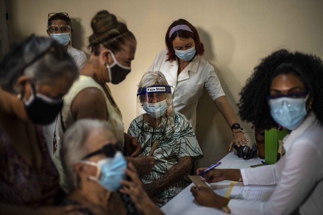 In this June 23, 2021 file photo, people sign up for a dose of the Cuban Abdala COVID-19 vaccine in Havana, Cuba. Cuba has been trying to rapidly roll out the two vaccines that it has approved for massive use, Abdala and Soberana, both of which require three jabs. (Photo by Ramon Espinosa/AP Photo/File)
