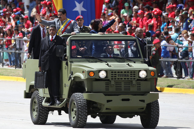 Venezuela's President Nicolas Maduro waves next to his wife Cilia Flores as they arrive to a military parade in Caracas, Venezuela February 1, 2017. (Photo by Carlos Garcia Rawlins/Reuters)