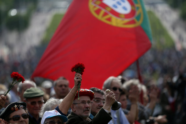 People, some holding red carnations, shout slogans during a march marking the international May Day, in Lisbon, Friday, May 1, 2015. (Photo by Francisco Seco/AP Photo)