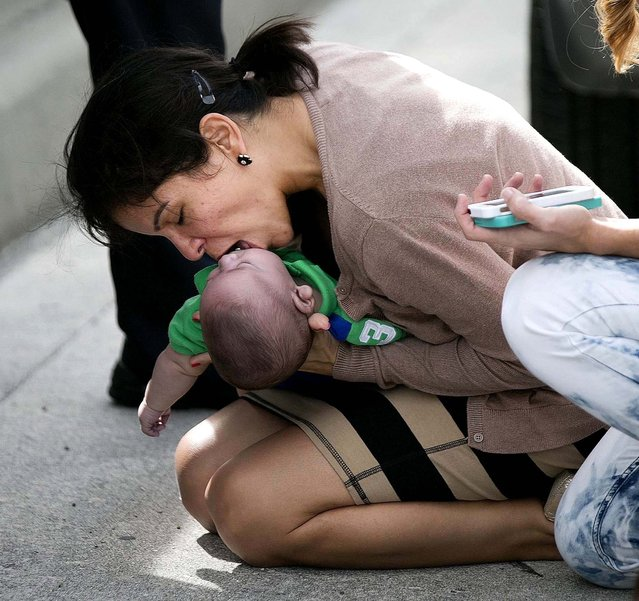 Pamela Rauseo performs CPR on her nephew, 5-month-old Sebastian de la Cruz, after pulling her SUV over on the side of the road along Florida State Road 836 in Miami, on February 20, 2014. (Photo by Al Diaz/Miami Herald/MCT)