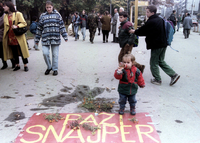 """Two-year-old Neira Kameric stands beside a mortar scar laid with flowers and a sign that reads """"Beware Sniper"""" in Sarajevo, November 1995. (Photo by Reuters)"""