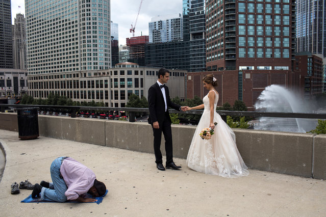 A Muslim taxi driver prays on the sidewalk while Tara and Soroush, two Iranian students who live downtown, celebrate their wedding day in Tehran, Iran. (Photo by Hossein Fatemi/Reuters/Panos Pictures/Courtesy of World Press Photo Foundation)