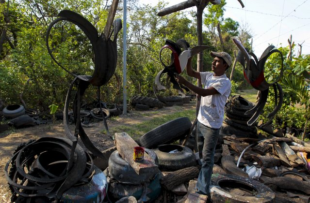 Josue Salazar (19), a student of agronomy, cuts a recycled tyre to make a bird figurine at a shop near Catarina town May 8, 2015. (Photo by Oswaldo Rivas/Reuters)