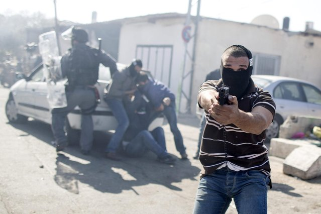 An Israeli undercover policeman point his gun while Israeli undercover policemen arrest a Palestinian stone thrower during clashes following Friday prayers at the east Jerusalem neighbourhood of Ras Al Amud, on 28 February 2014. Several Palestians were arrested for stone throwing at the Jerusalem Old City area after the Israeli Police restricted the entrance to the Al-Aqsa mosque and permitted only men over the age of 50. (Photo by Abir Sultan/EPA)