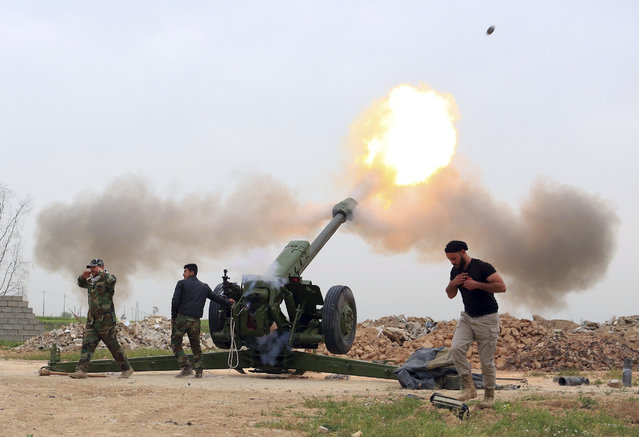 Iraqi security forces fire at Islamic State militants positions from villages south of the Islamic State group-held city of Mosul, Iraq, Saturday, March 26, 2016. The Iraqi military backed by U.S.-led coalition aircraft on Thursday launched a long-awaited operation to recapture the northern city of Mosul from Islamic State militants, a military spokesman said. (Photo by AP Photo/Stringer)