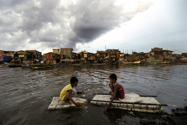 Young Filipinos paddle next to secured boats awaiting the arrival of typhoon Noul in Navotas city, north of Manila, Philippines, 10 May 2015. A strong typhoon barrelled into the north-eastern Philippines, ripping off rooves and forcing thousands of people to flee their homes, disaster relief officials said. (Photo by Ritchie B. Tongo/EPA)