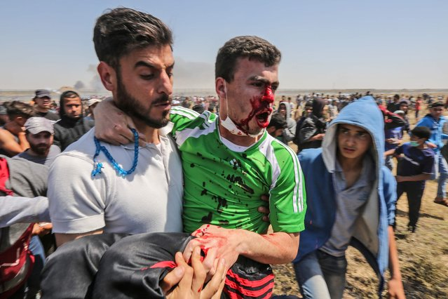 A wounded Palestinian demonstrator is carried away from the border fence during clashes with Israeli forces east of Gaza City in the Gaza Strip on May 15, 2019, following a protest marking 71th anniversary of Nakba – also known as Day of the Catastrophe in 1948. (Photo by Mahmud Hams/AFP Photo)