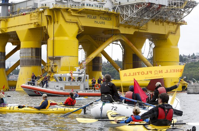 The U.S. Coast Guard monitors activists as they take to the water to protest the Shell Oil Company's drilling rig Polar Pioneer which is parked at Terminal 5 at the Port of Seattle, Washington May 16, 2015. (Photo by Jason Redmond/Reuters)