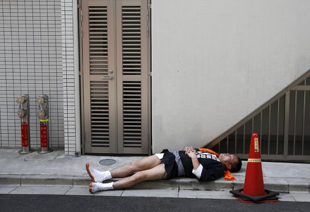 A reveller sleeps on the pavement during the Sanja Matsuri festival in the Asakusa district of Tokyo May 17, 2015. The Sanja Matsuri festival attracts over about one million visitors over its duration of three days, when parties of revellers carry portable shrines through the Asakusa neighbourhood, rocking and shaking them in a belief that this intensified the powers of the deities that reside inside them. (Photo by Thomas Peter/Reuters)