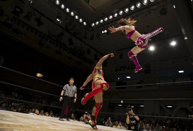 Wrestler Kaori Housako jumps at her opponent Mieko Satomura during a Stardom female professional wrestling show at Korakuen Hall in Tokyo, Japan, July 26, 2015. (Photo by Thomas Peter/Reuters)