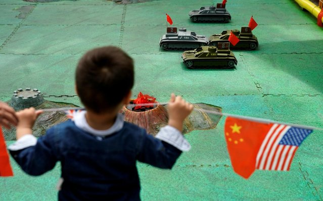 A boy looks at remote control tank toys next to the flags of China and the U.S. at a park in Shanghai, China, May 29, 2019. (Photo by Aly Song/Reuters)