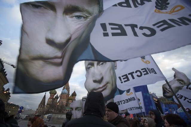 """People rally in support of Crimea joining Russia, with banners and portraits of Russian President Vladimir Putin, reading """"We are together"""", in Red Square in Moscow, Tuesday, March 18, 2014.  With a sweep of his pen, President Vladimir Putin added Crimea to the map of Russia on Tuesday, describing the move as correcting past injustice and responding to what he called Western encroachment upon Russia's vital interests. (Photo by Pavel Golovkin/AP Photo)"""