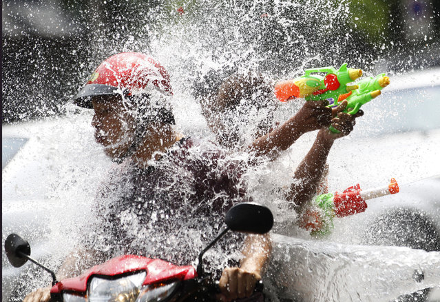 In this April 13, 2015 file photo, people riding on a motorbike react as a boy splashes water on them during the traditional Thai New Year celebrations or Songkran water festival in Bangkok. Thailand's military government is putting a dampener on the annual nationwide water fight. Despite Thailand's worst drought in 20 years, the junta says it has no intention of limiting the virtually around-the-clock water throwing that defines the three-day Songkran festival. Instead, it has decided to impose morality measures. (Photo by Sakchai Lalit/AP Photo)