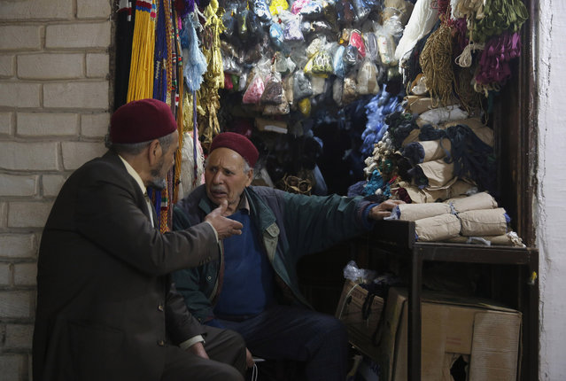 Tunisian vendors talk to each other outside their shop, in the Old City of Tunis, Tunisia, Thursday, March 28, 2019. (Photo by Hussein Malla/AP Photo)