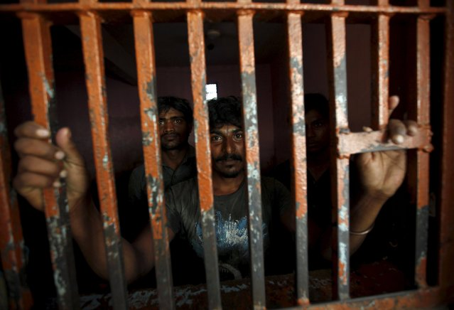 Fishermen from India stand behind bars in a lockup, after being detained in Pakistani waters, at a police station in Karachi April 18, 2015. According to local media, Pakistan maritime authorities arrested 47 Indian fishermen and took into custody their eight boats for illegal fishing in the country's territorial waters, police said on Saturday. (Photo by Akhtar Soomro/Reuters)