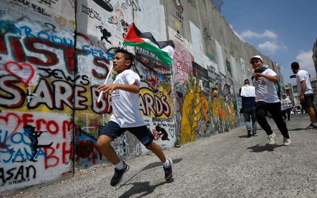 """A Palestinian boy runs with his national flag along Israel's controversial separation barrier, which divides the occupied West Bank from Jerusalem, during the """"Run for Freedom"""" marathon in Bethlehem on June 16, 2019, in protest against Trump's expected peace plan proposal. (Photo by Musa Al Shaer/AFP Photo)"""