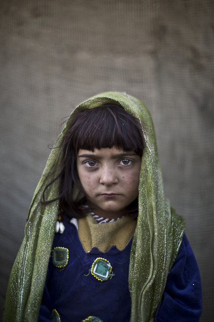 In this Saturday, January 25, 2014 photo, Afghan refugee girl, Zarlakhta Nawab, 6, poses for a picture, while playing with other children in a slum on the outskirts of Islamabad, Pakistan. (Photo by Muhammed Muheisen/AP Photo)