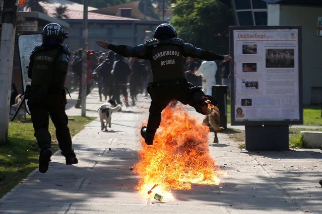A riot policeman jumps over a molotov bomb during clashes with student protesters during a demonstration to demand changes in the education system in Santiago, Chile, April 21, 2016. (Photo by Clemente Villavicencio/Reuters)