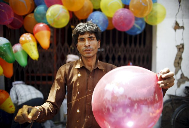A man ties a balloon near the cracked wall of a house as he inflates them during an event organized to commemorate the victims of last year's earthquakes in Kathmandu, Nepal, April 23, 2016. (Photo by Navesh Chitrakar/Reuters)