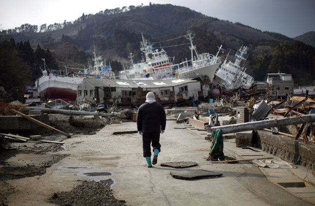 A man walks next to port area destroyed by the earthquake and tsunami in Kessenuma town, in Miyagi prefecture March 28, 2011. (Photo by Carlos Barria/Reuters)