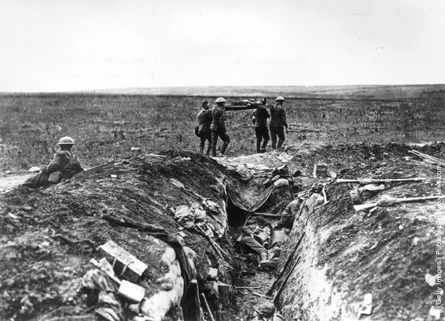 1915: A wounded British soldier is stretchered back to camp past a carnage-strewn trench, during the First World War