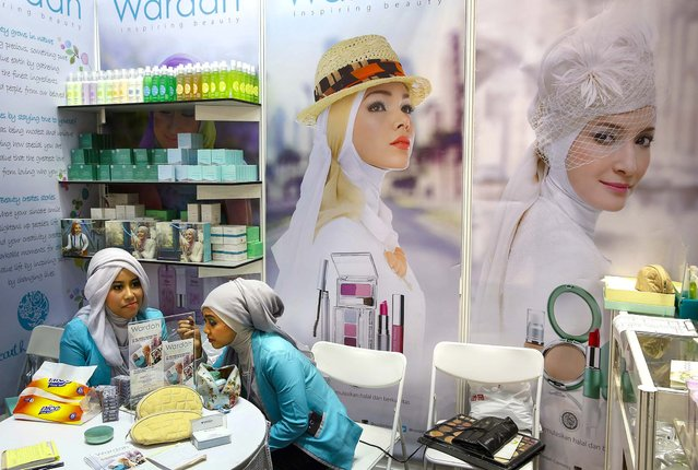 A vendor touches up her make-up while waiting for customers during the Malaysia International Halal Showcase in Kuala Lumpur, on April 9, 2014. (Photo by Vincent Thian/Associated Press)