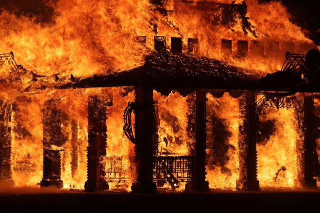 """The """"Temple of Time"""" built as a memorial to the 17 victims of a shooting at Marjory Stoneman Douglas High School is seen on fire during a ceremonial burning in Coral Springs, Fla., Sunday, May 19, 2019. The """"Temple of Time"""" public art installation was set on fire Sunday at the ceremony hosted by the cities of Parkland and Coral Springs, where the high school's students live. (Photo by John McCall/South Florida Sun-Sentinel via AP Photo)"""