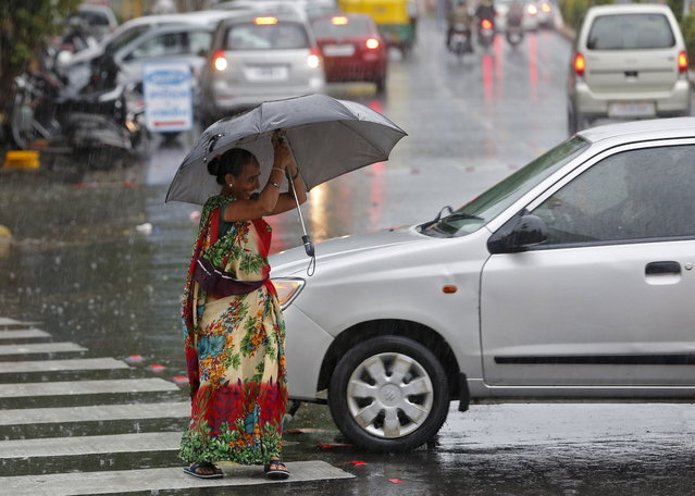 A woman tries to hold an umbrella as she walks through a busy road during a rain shower in Ahmedabad, June 24, 2015. (Photo by Amit Dave/Reuters)