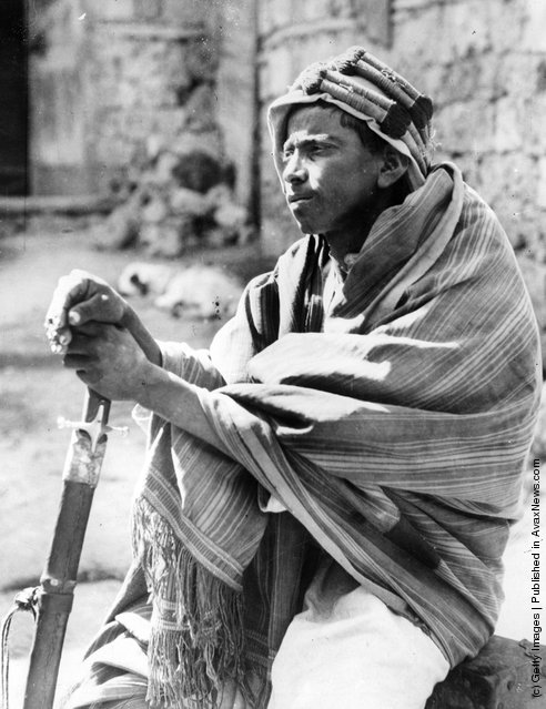 1930: A young bedouin 'spy' in Jiddah (Jedda) leans on his sword as he keeps watch