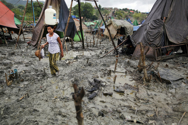 A woman carries a canister of clean water through the mud of an oil field in the Minhla township of the Magwe district October 27, 2013. (Photo by Damir Sagolj/Reuters)