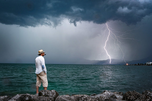 A man stands on rocks as lightning strikes over Lake Geneva on August 6, 2019 near Le Bouveret, western Switzerland. (Photo by Fabrice Coffrini/AFP Photo)