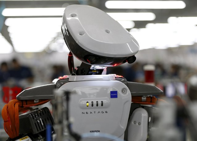 A humanoid robot is seen in the assembly line at a factory of Glory Ltd., a manufacturer of automatic change dispensers, in Kazo, north of Tokyo, Japan, July 1, 2015. (Photo by Issei Kato/Reuters)