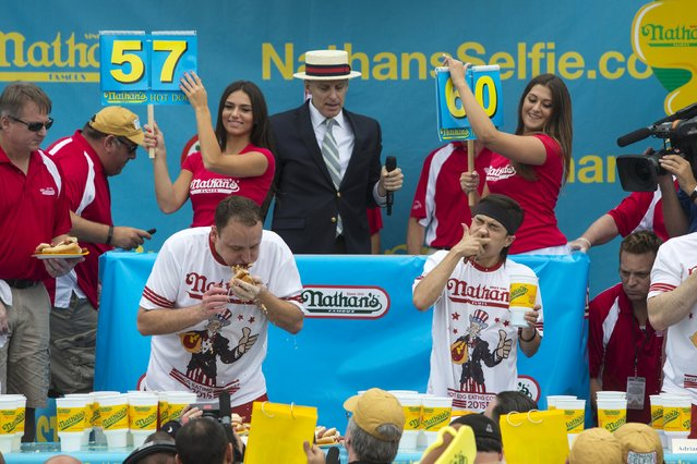 Joey Chestnut (L) and Matt Stonie (R) consume hot dogs during the annual Fourth of July 2015 Nathan's Famous Hot Dog Eating Contest in Brooklyn, New York July 4, 2015. (Photo by Andrew Kelly/Reuters)