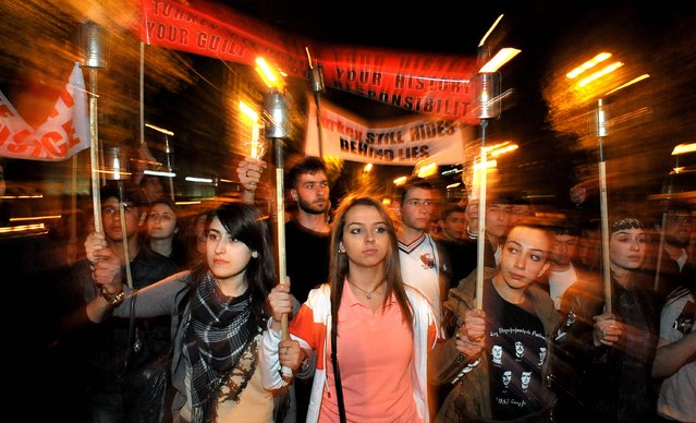 """Armenian women carry torches to commemorate the 99th anniversary of the Ottoman Turkish massacre of Armenians, in Yerevan on April 23, 2014. Turkish Prime Minister Recep Tayyip Erdogan offered condolences over the massacre of Armenians almost 100 years ago, describing the events of World War I as """"our shared pain"""". (Photo by Karen Minasyan/AFP Photo)"""