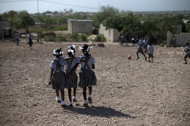 In this June 24, 2015 photo, schoolgirls walk through the rocky yard of Bethesda Evangelical School during a break in class, in Canaan, Haiti. (Photo by Rebecca Blackwell/AP Photo)