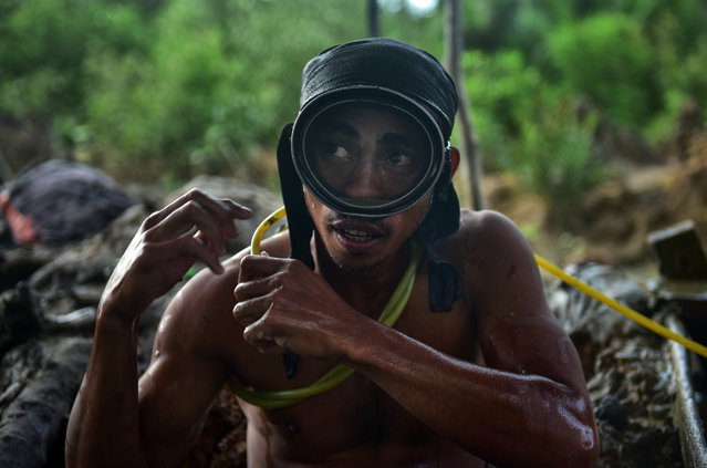 Anthony Balderosdasco, 28, readies himself to dive down beneath the mud to look for gold on March 22, 2017 in Paracale, Philippines. (Photo by Jes Aznar/Getty Images)