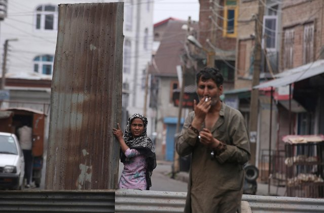 A Kashmiri woman reinforces a barrier to prevent security personnel from entering her neighborhood after the scrapping of the special constitutional status for Kashmir by the Indian government, in Srinagar, August 28, 2019. (Photo by Danish Ismail/Reuters)