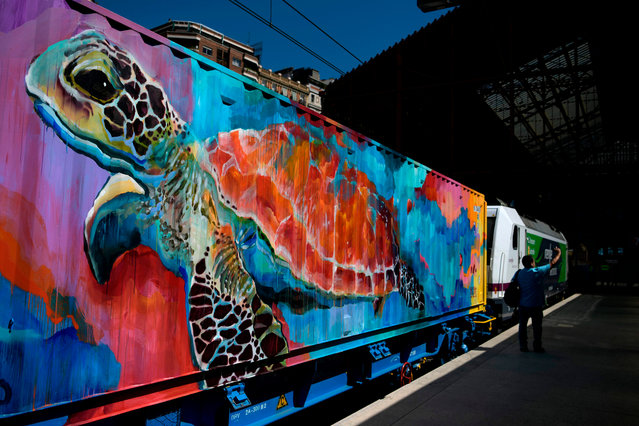 A man takes a picture from the platform, in front of the so-called Noah's Train, a 200-metre long freight train with wagons designed by street artists, at the Principe Pio train station in Madrid, on September 5, 2019. The initiative launched by the Rail Freight Forward (RFF), is the world's longest mobile artwork aimed at bringing attention to the coalition's goal of shifting 30% of freight to rail by 2030, and underlines its commitment to more climate protection and the conservation of endangered species. Renfe Mercancias and Transfesa Logistics rail transport companies, joined the RFF coalition. (Photo by Gabriel Bouys/AFP Photo)