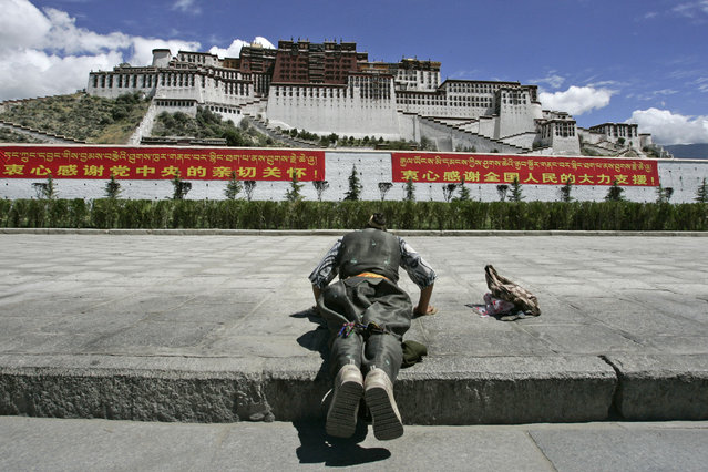 Potala Palace: A Tibetan pilgrim prays in front of the Potala Palace in Lhasa in Tibet Autonomous Region July 5, 2006. (Photo by Claro Cortes IV/Reuters)