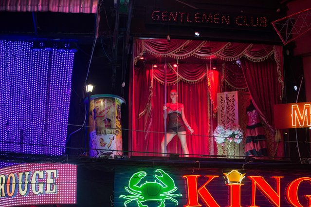 This photo taken on March 29, 2017 shows a woman dancing on a stage above Walking Street in Pattaya in an effort to attract customers to a bar. (Photo by Roberto Schmidt/AFP Photo)