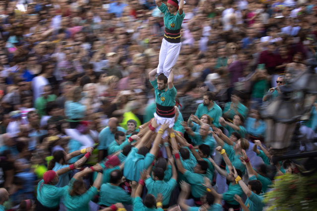 "Participants walk maintaining a human tower or ""Castellers"" during the Saint Merce celebrations in San Jaume square in Barcelona, Spain, Tuesday, September 24, 2019. The tradition of building human towers or ""castells"" dates back to the 18th century and takes place during festivals in Catalonia, where ""colles"" or teams compete to build the tallest and most complicated towers. (Photo by Emilio Morenatti/AP Photo)"